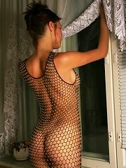 Beautiful nude girl posing in a fishnet dress