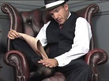 Gay hunk wearing pin striped suit playing with his feet and cock