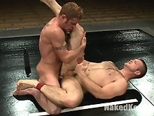Two studs with huge boners fight naked in oil.