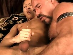 A big hairy bear pleases a young asian dude while that one jerking his hard dick and cumming over himself
